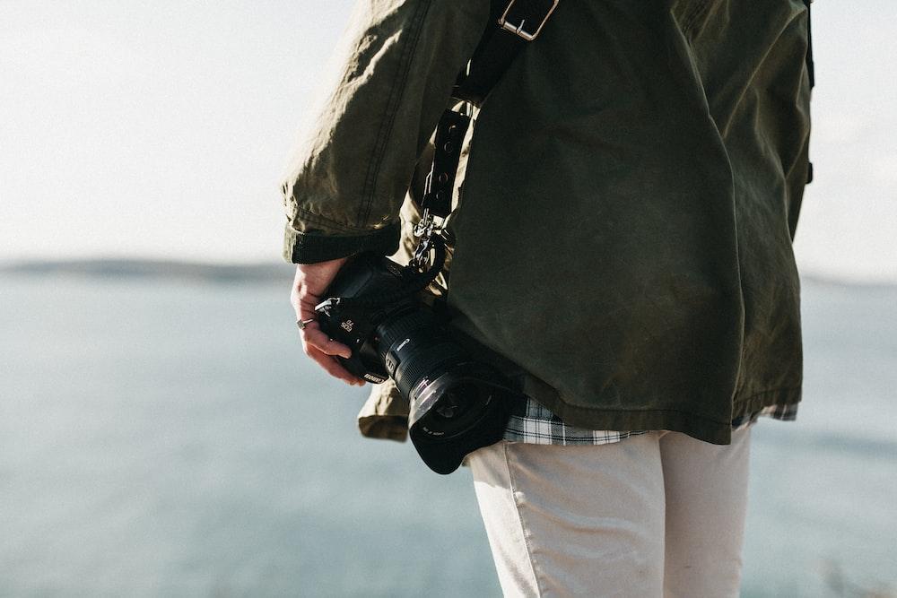 person with black camera photo