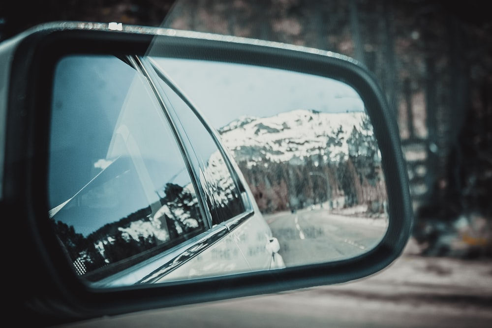 snow-capped mountain view from gray vehicle's right side mirror