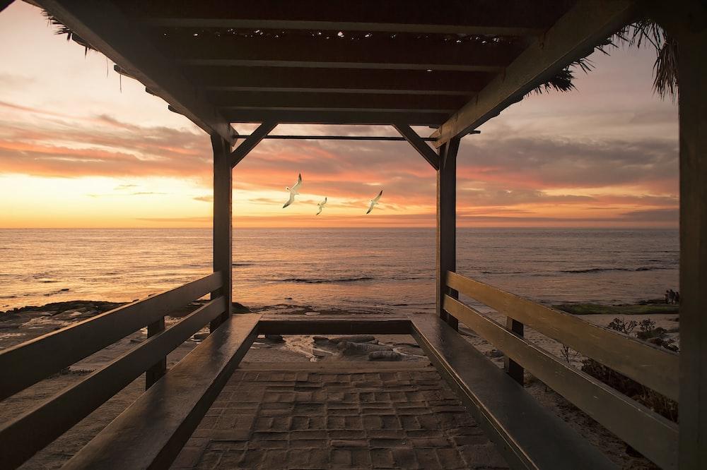 brown wooden hut beside seashore during orange sunset