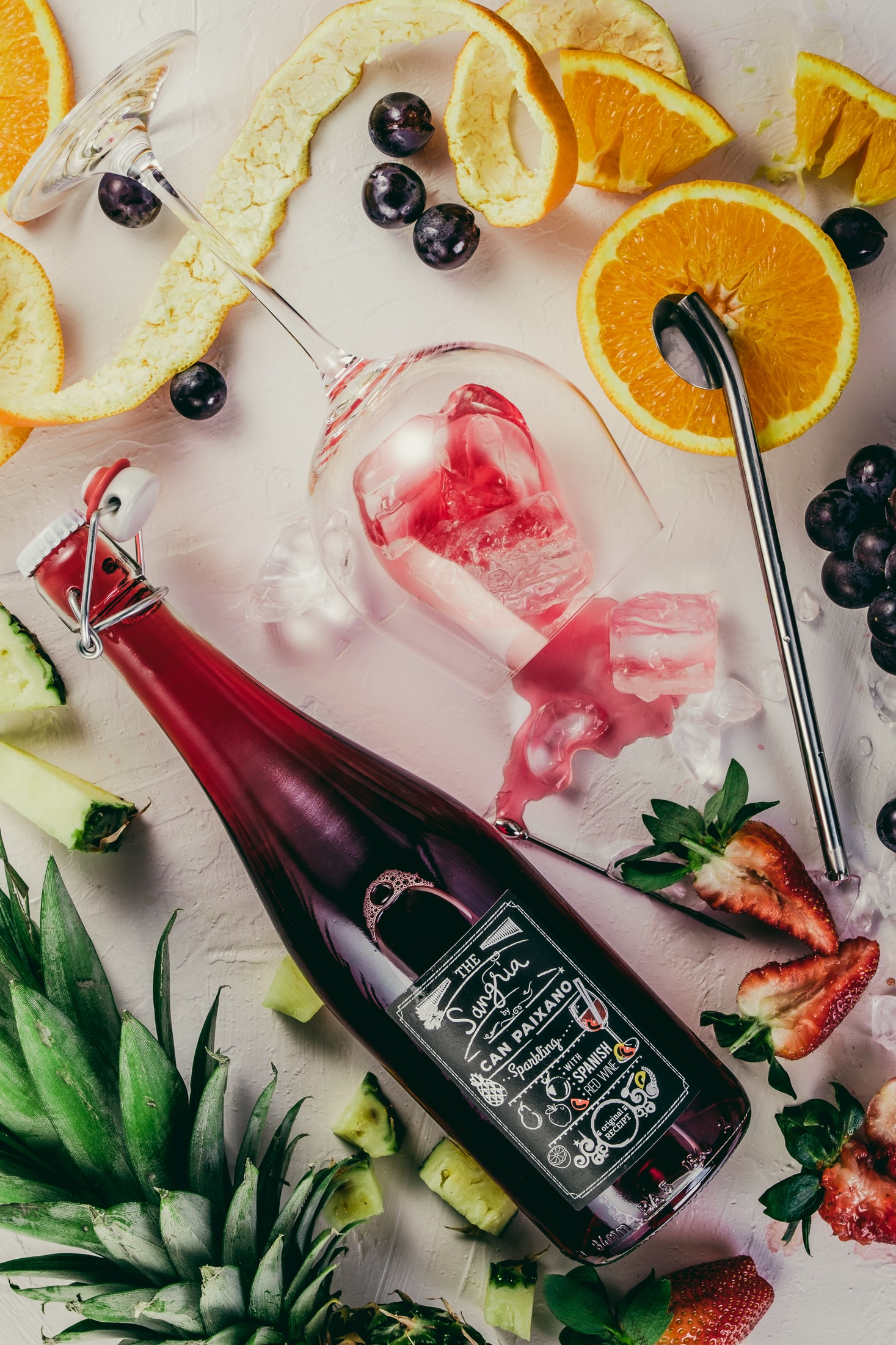 flat-lay photograph of sliced fruits, swing top bottle, and wine glass