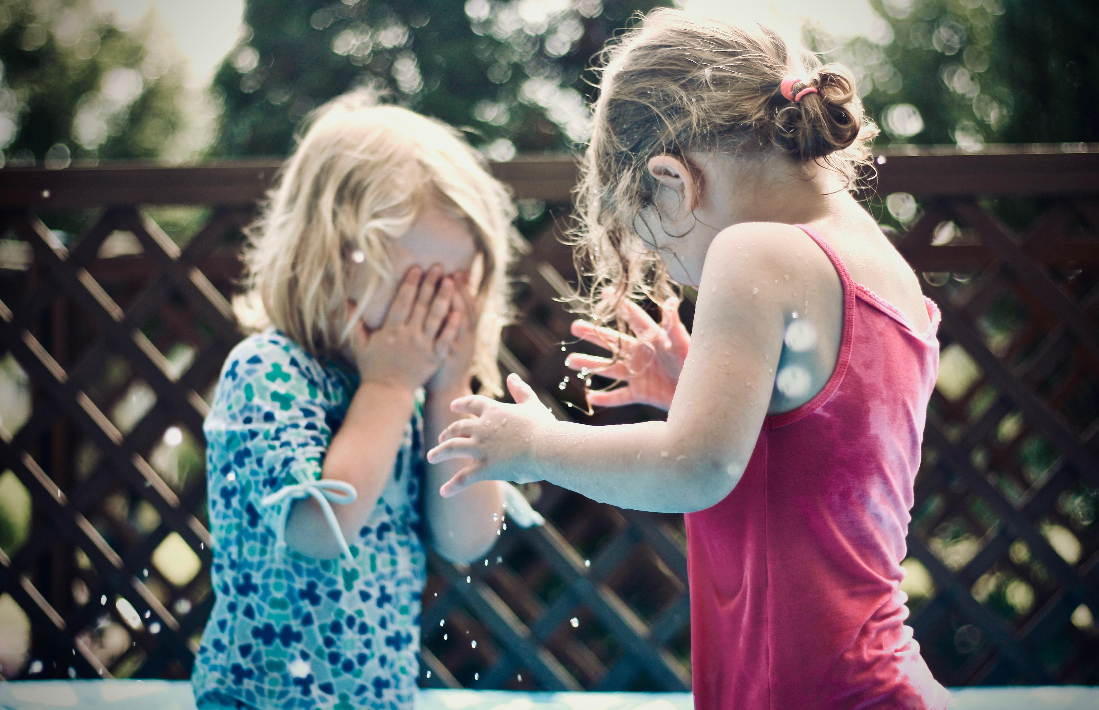 two children playing water during daytime shallow focus photography