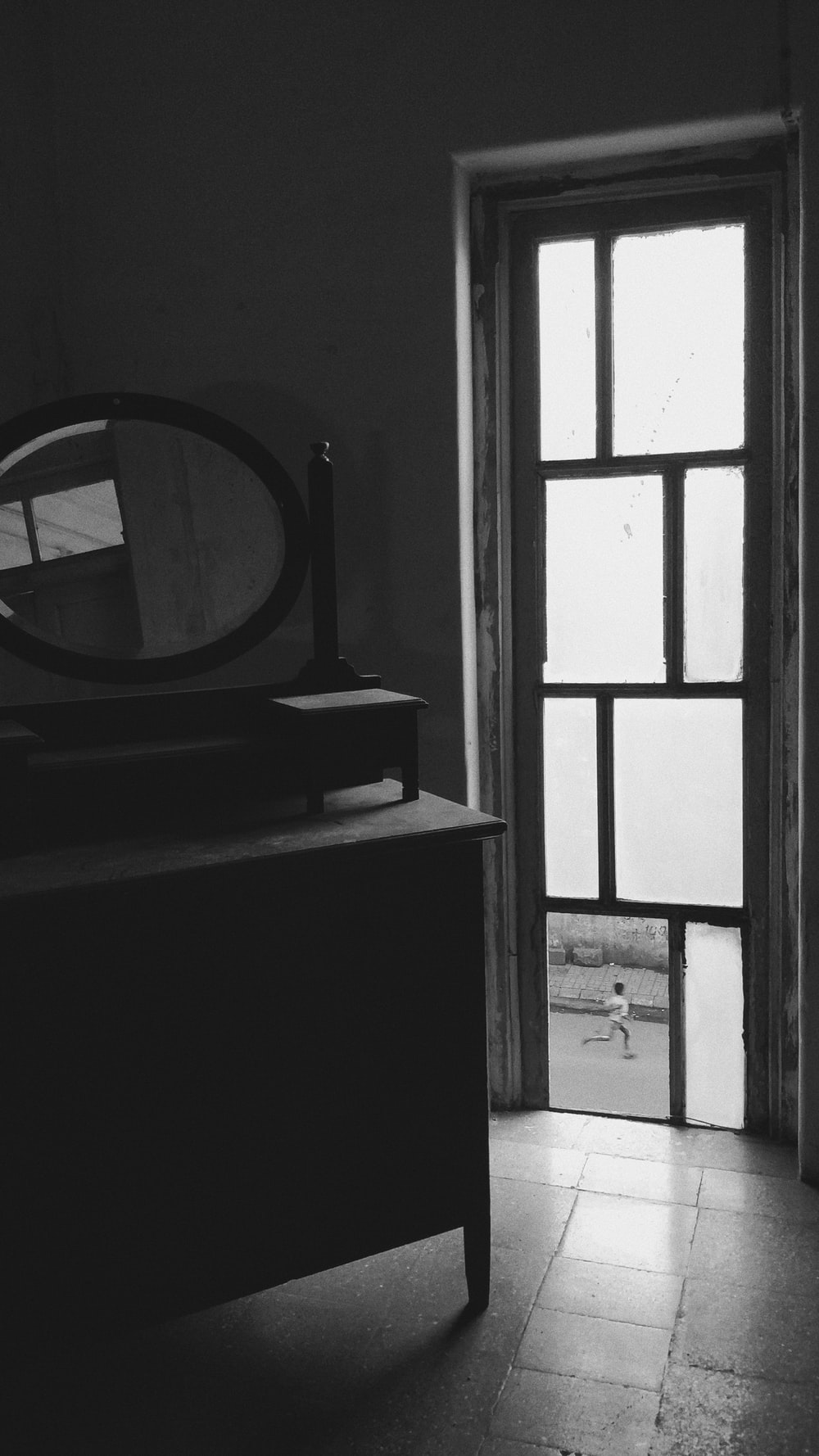 grayscale photo of dresser with mirror