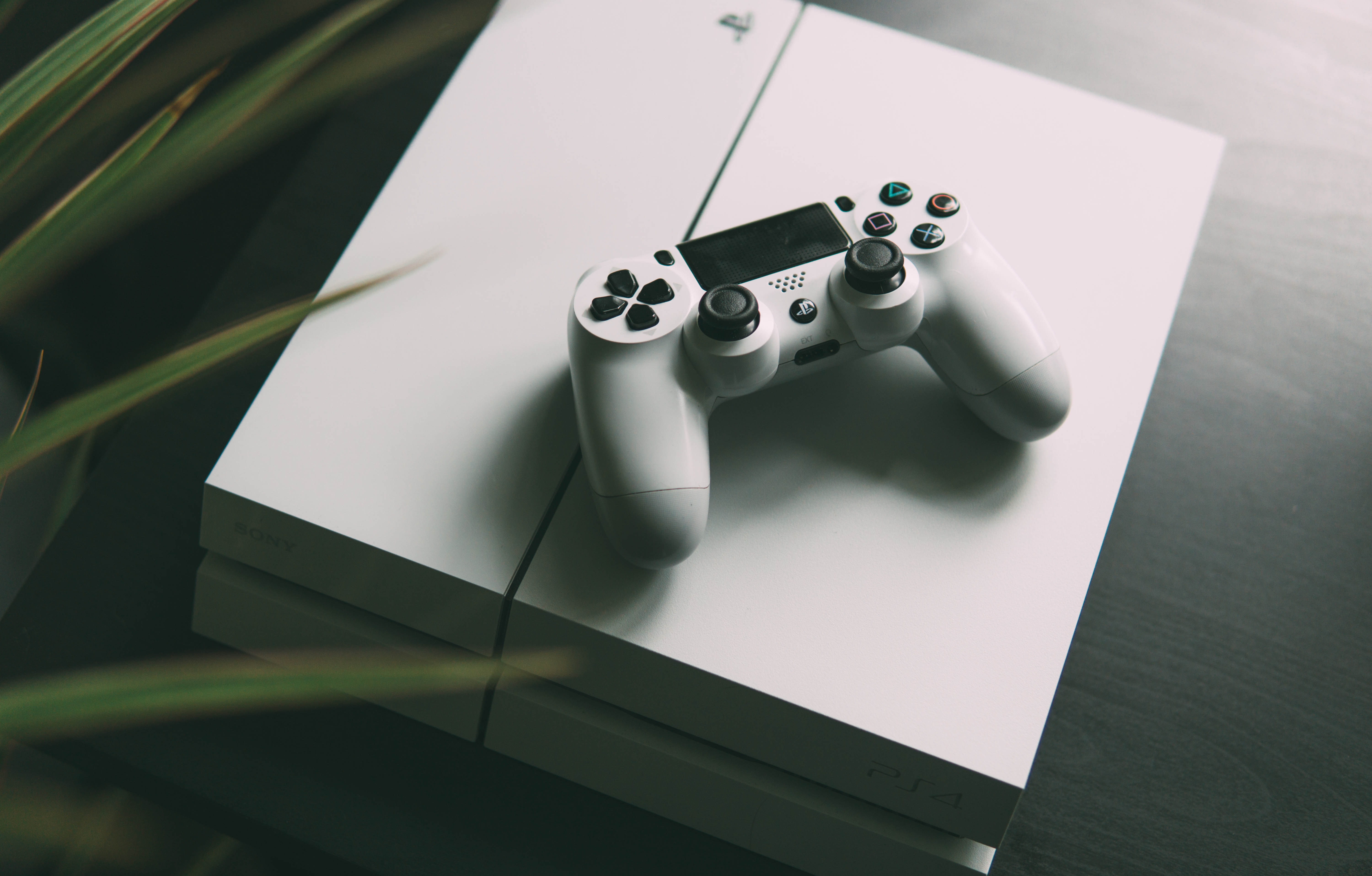 selective focus photography of white Sony PS4 console with wireless controller