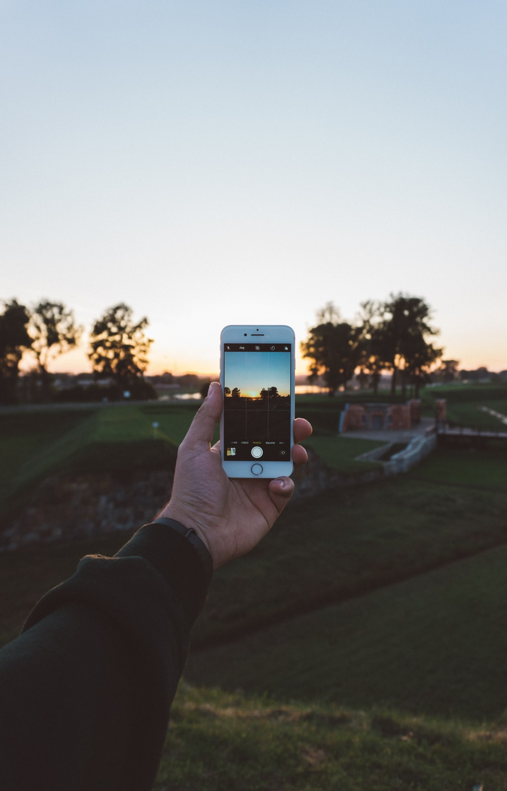 person holding iPhone white taking picture during daytime