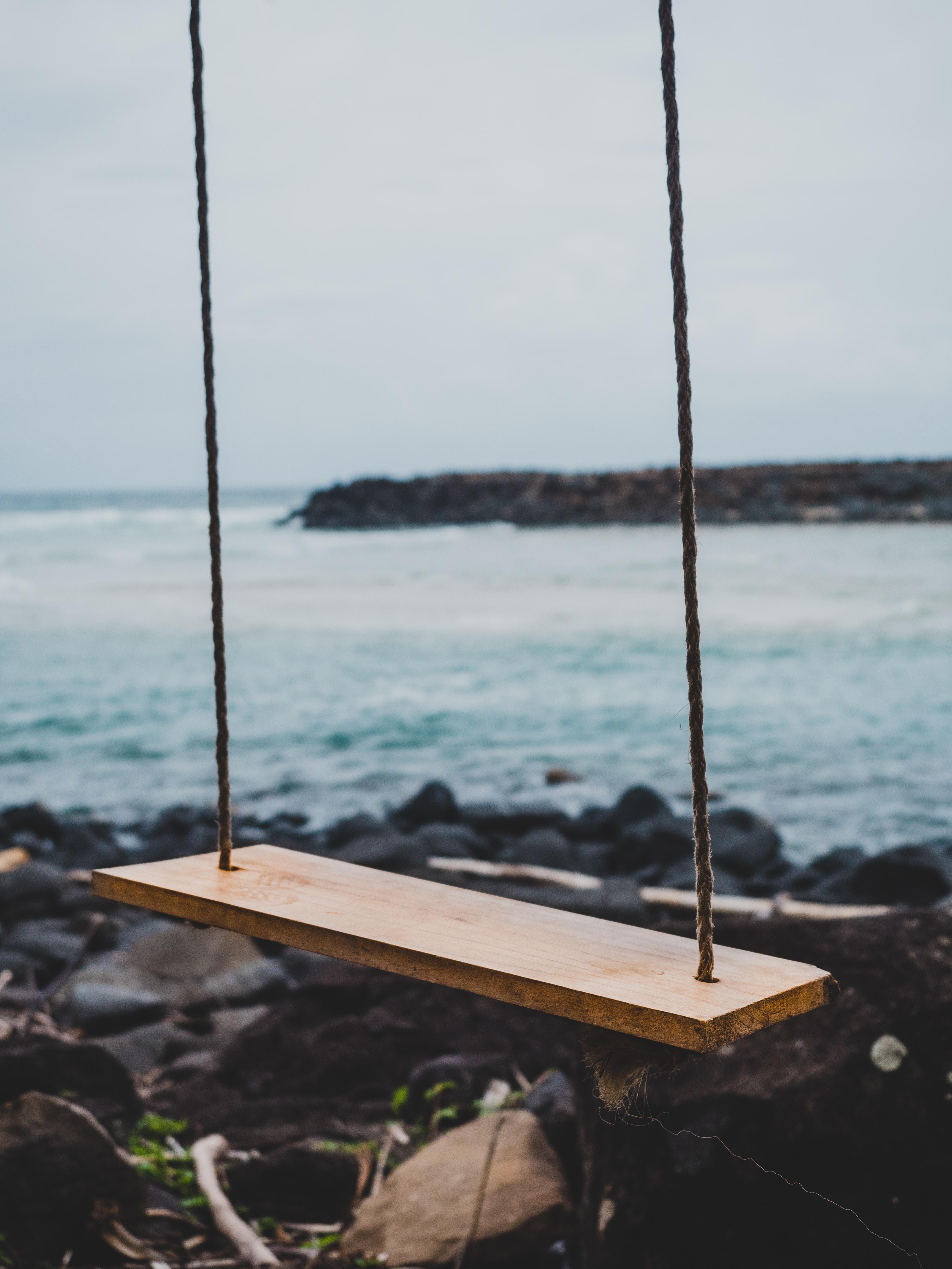 brown wooden swing chair beside shoreline