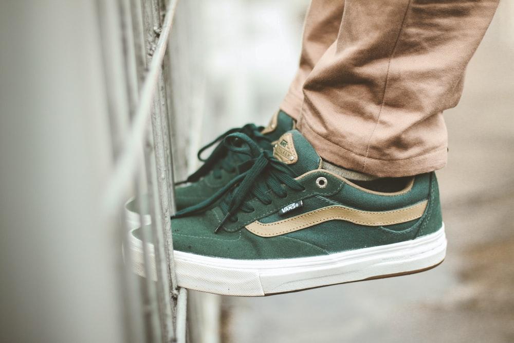 person wearing green Vans low-top sneakers