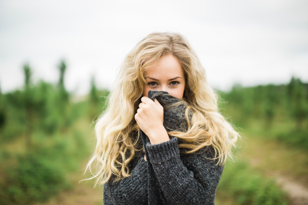 Photo Via: Unsplash.com Courtney Clayton @courtneyrclayton, woman wearing sweater and covering face.