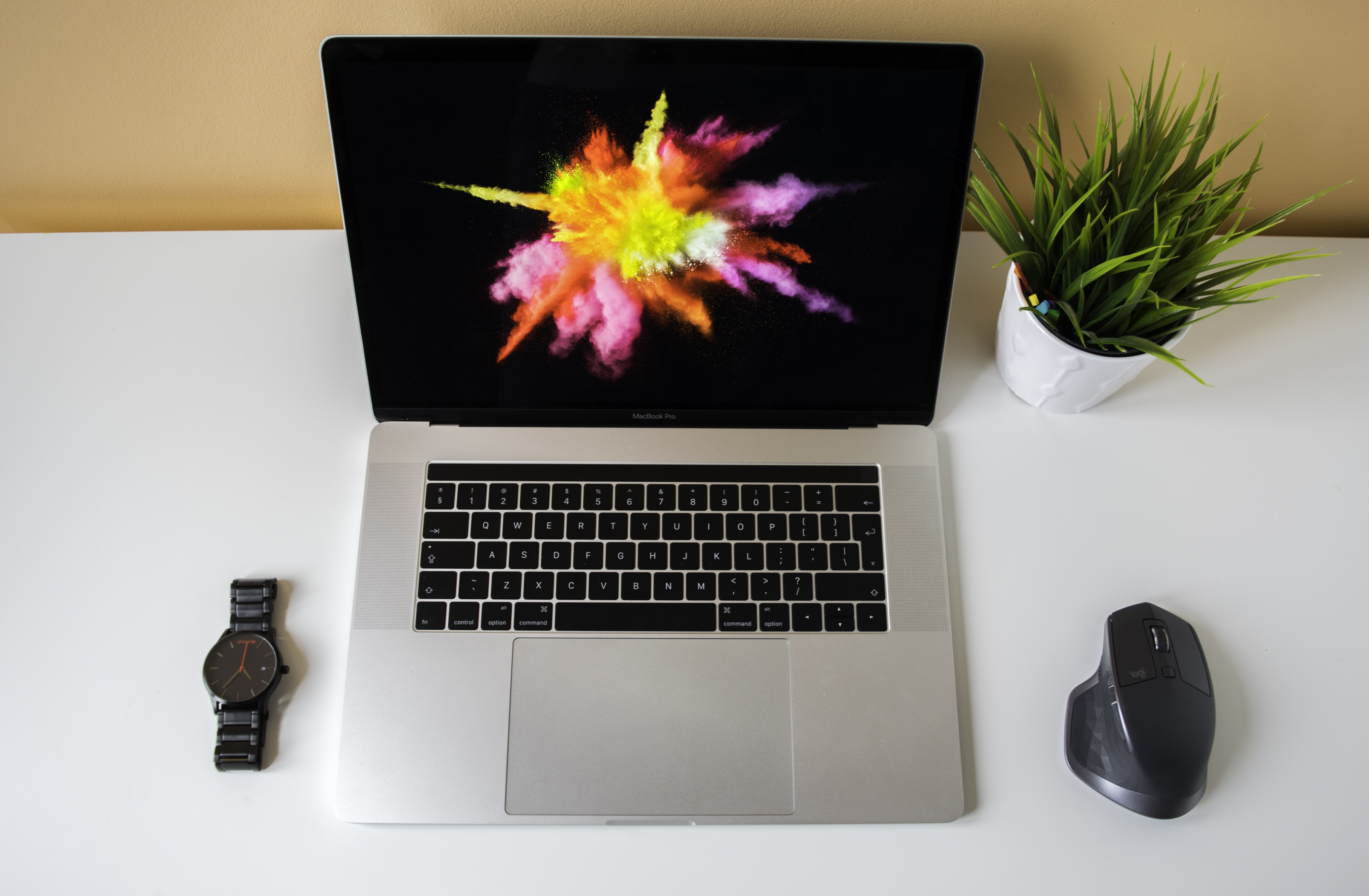 flat lay photography of MacBook Pro in between mouse and watch