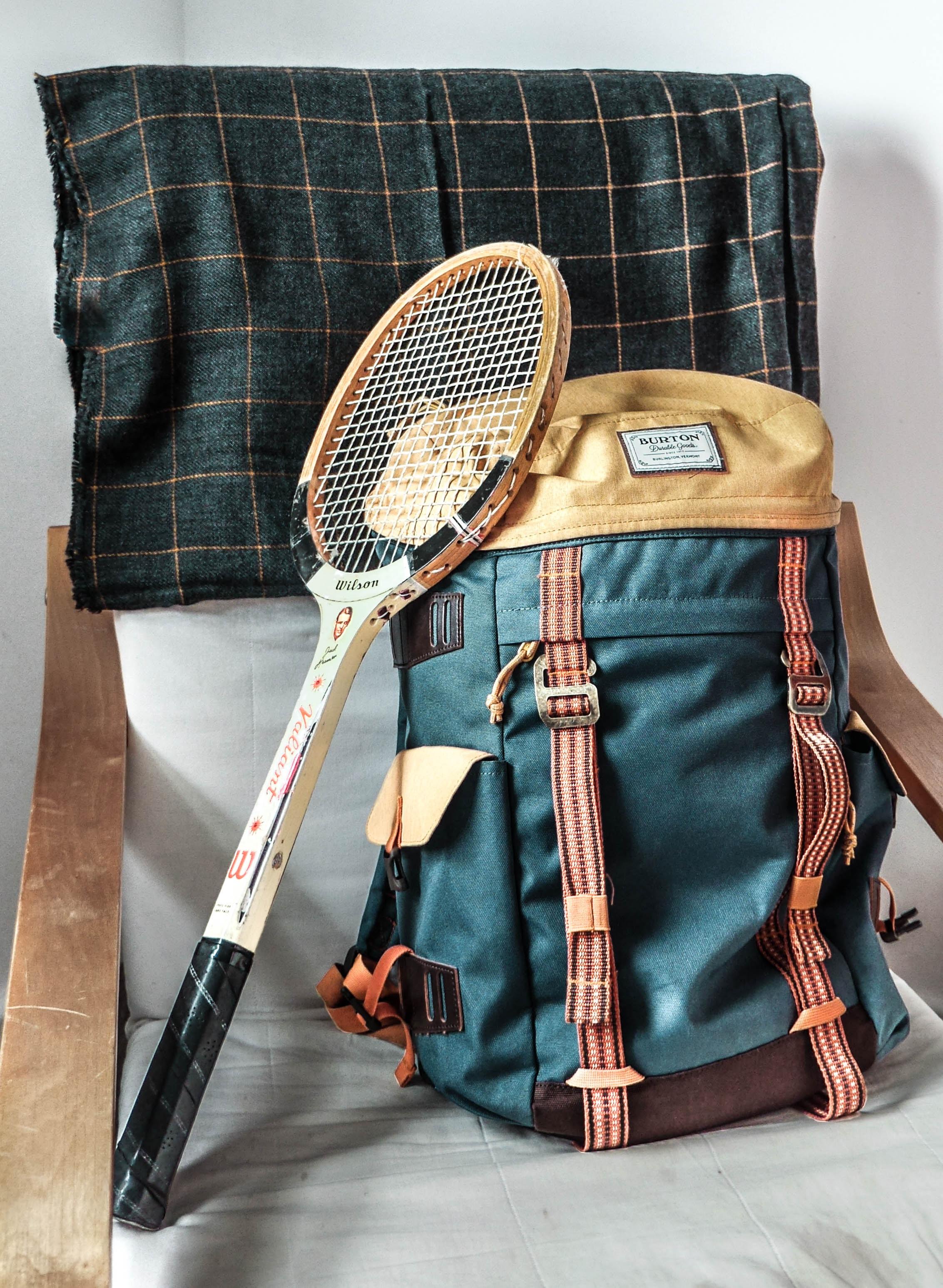 vintage brown tennis racket and green hiking backpack