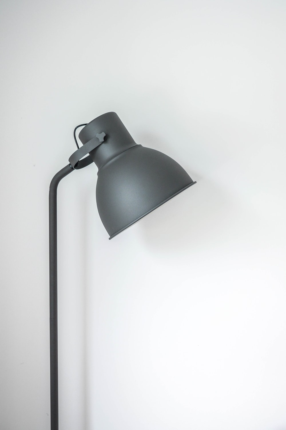 gray desk lamp near white wall