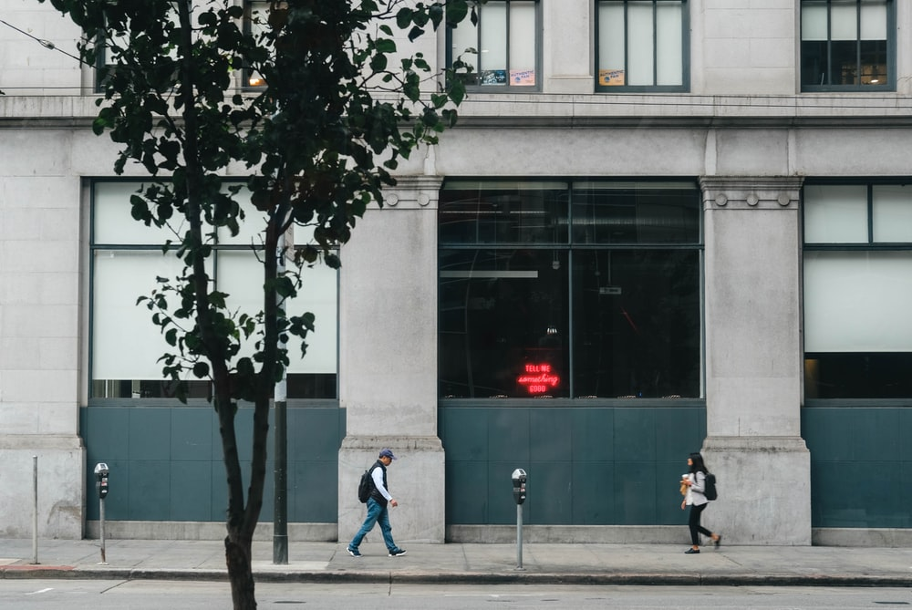 two man and woman walking near grey concrete building