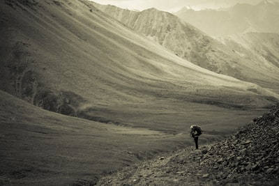 grayscale photo of person walking on mountain feet during daytime kyrgyzstan teams background