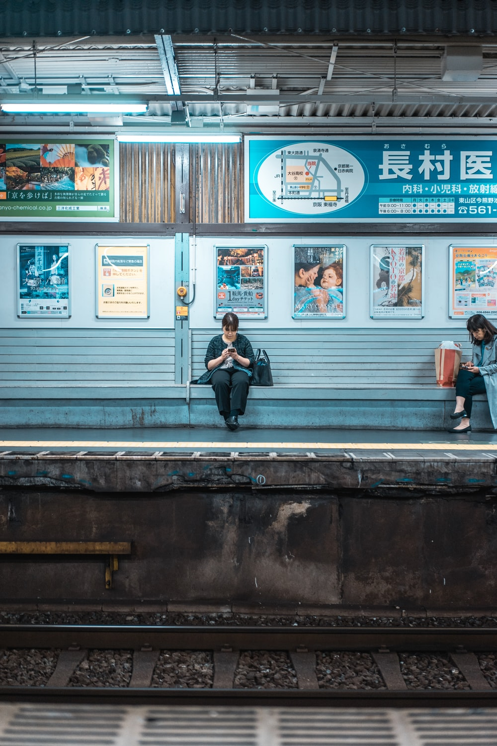 woman sitting on bench while using phone