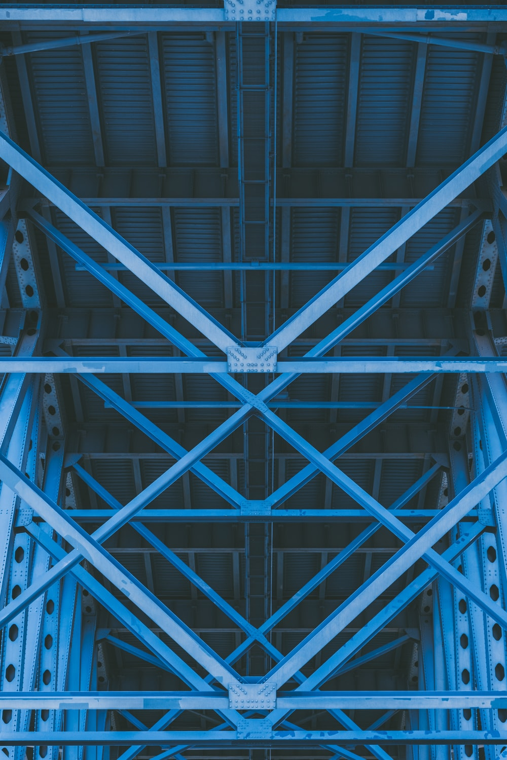 low-angle photography of grey metal beams and roof