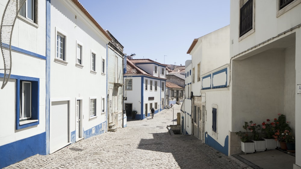 grey road lined with white and blue concrete houses at daytime