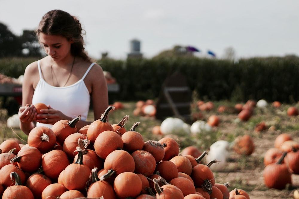 woman choosing from pile of pumpkins