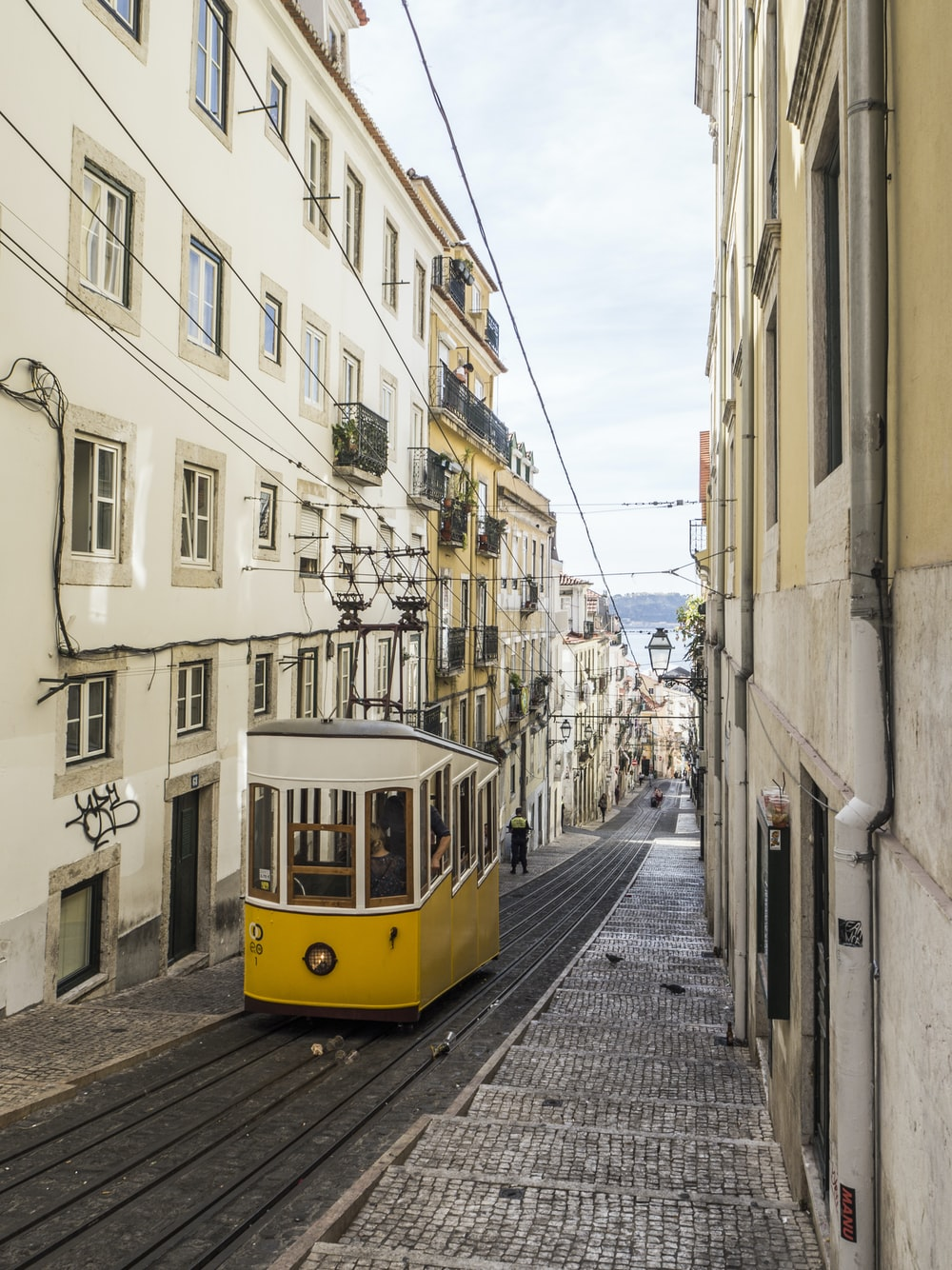 yellow and white bus in the middle of white buildings during daytime