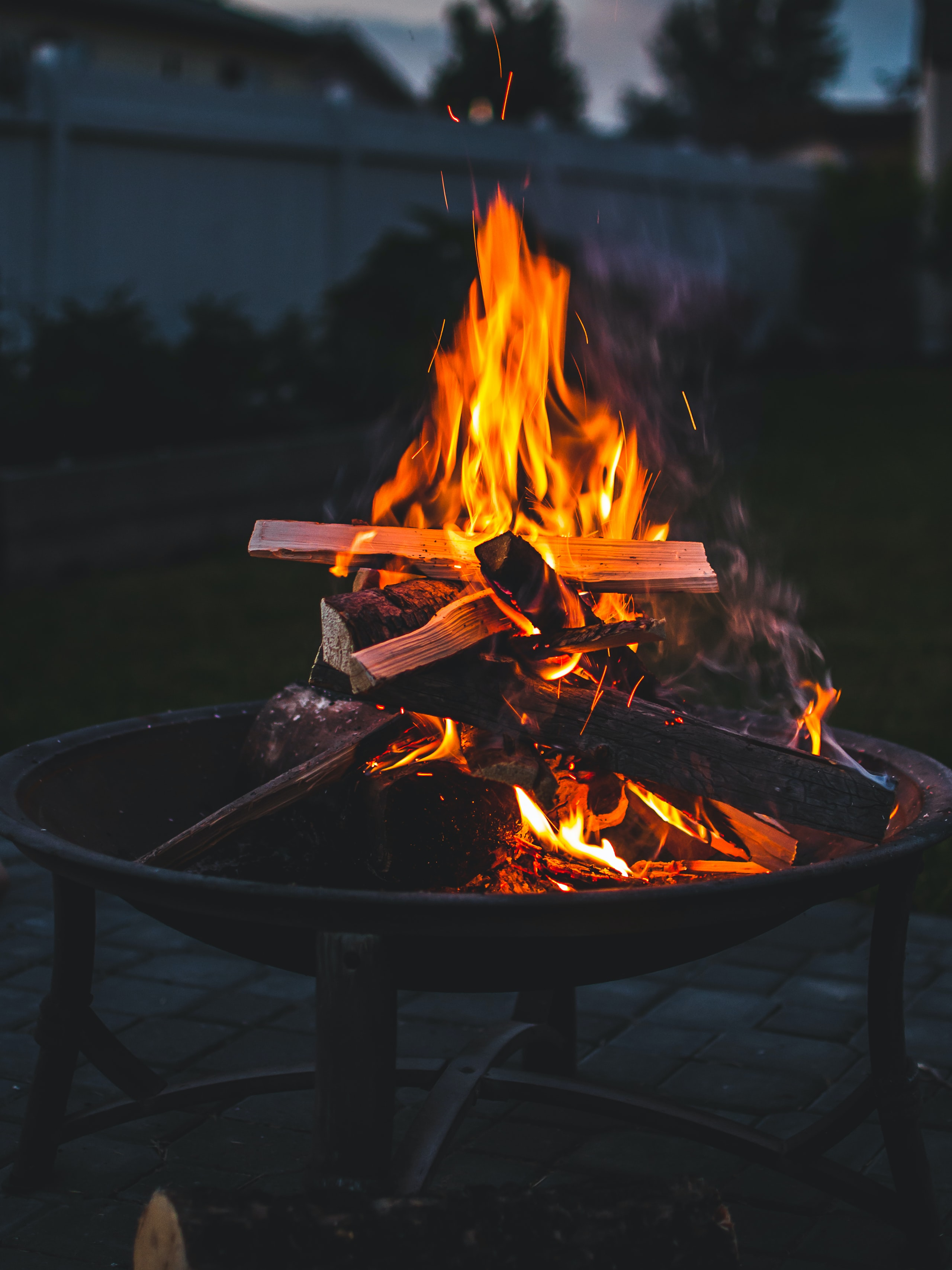 bonfire on brown steel fire pit during sunset