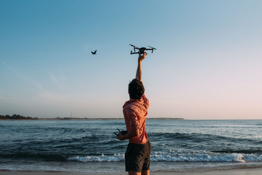 man holding drone near the ocean