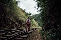 woman walking on train trail at daytime