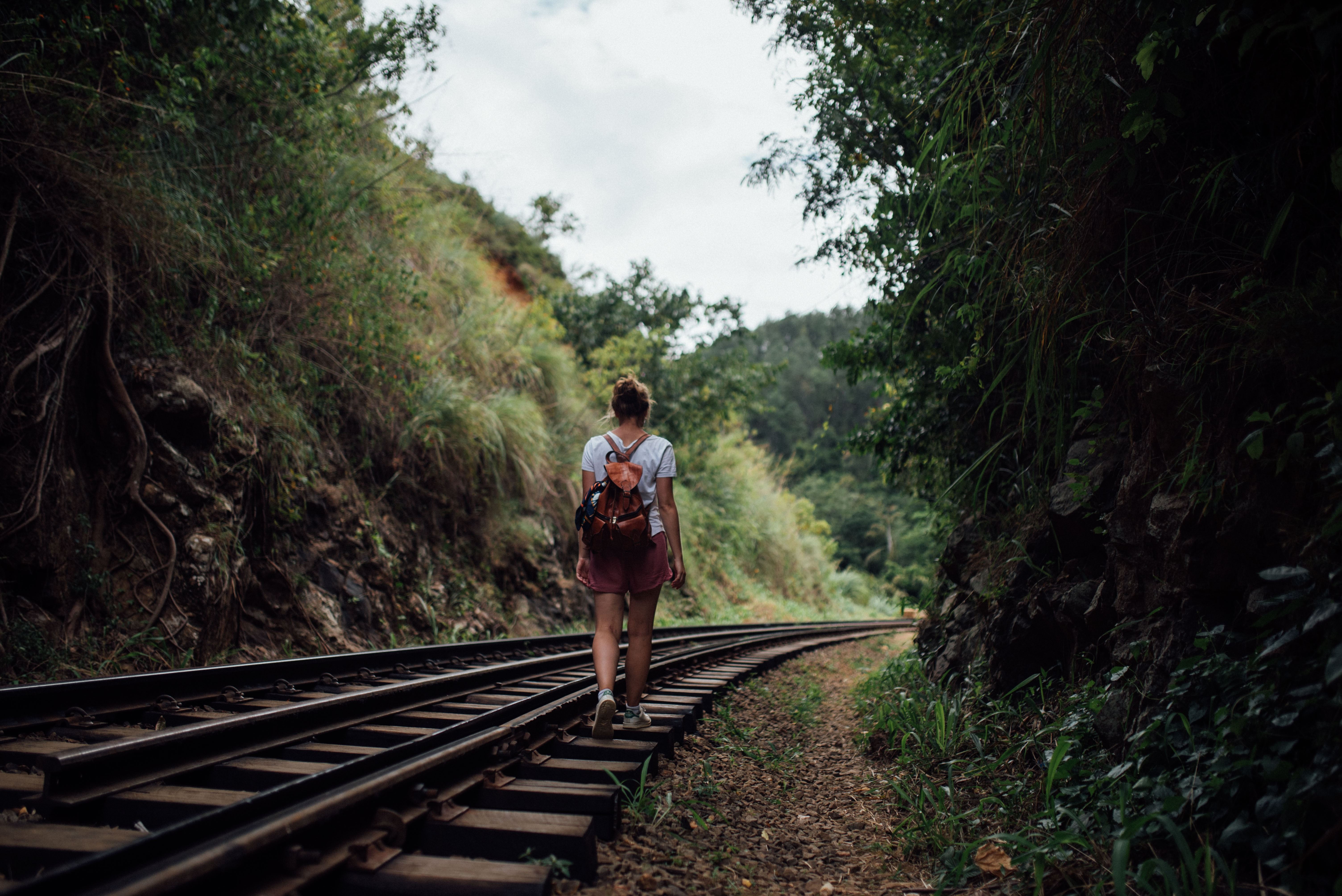 woman walking on train trail at daytime