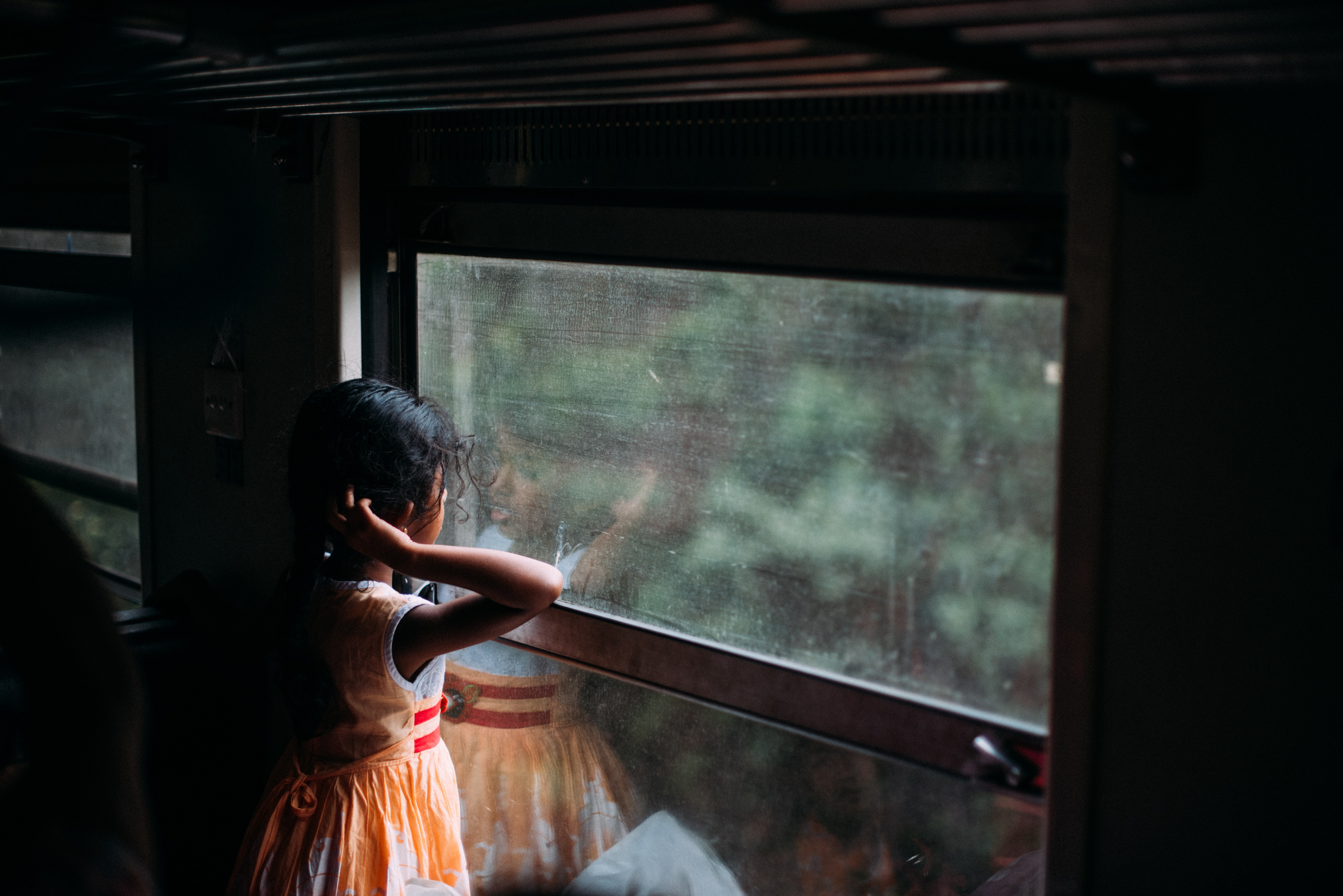 girl in orange sleeveless dress looking at the window