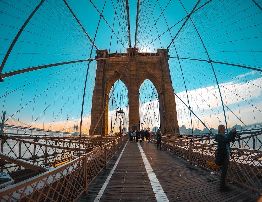 people standing on brown concrete bridge