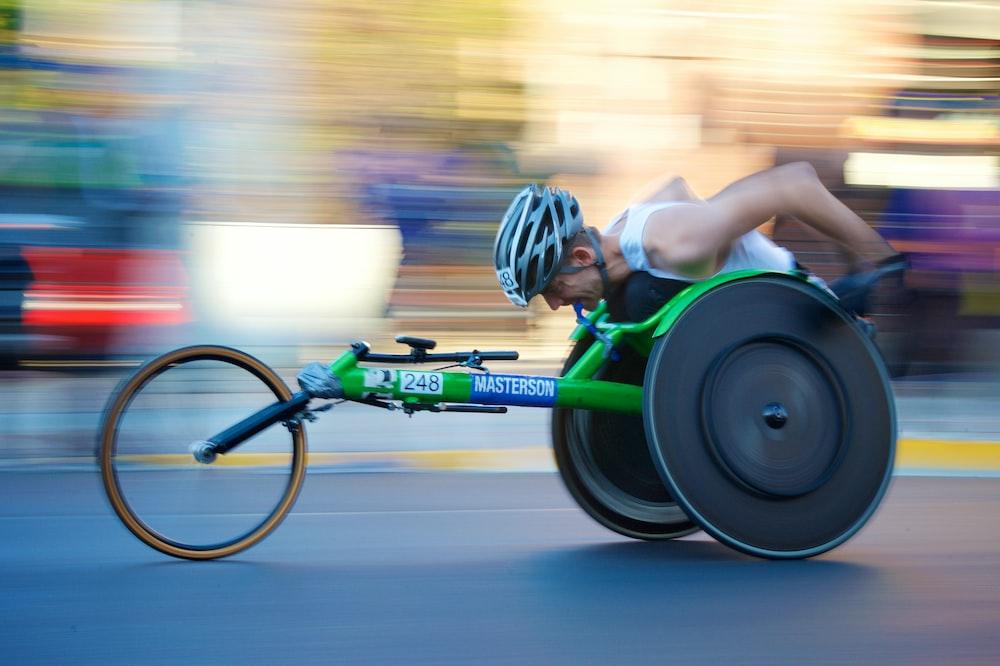 man riding green racing wheelchair