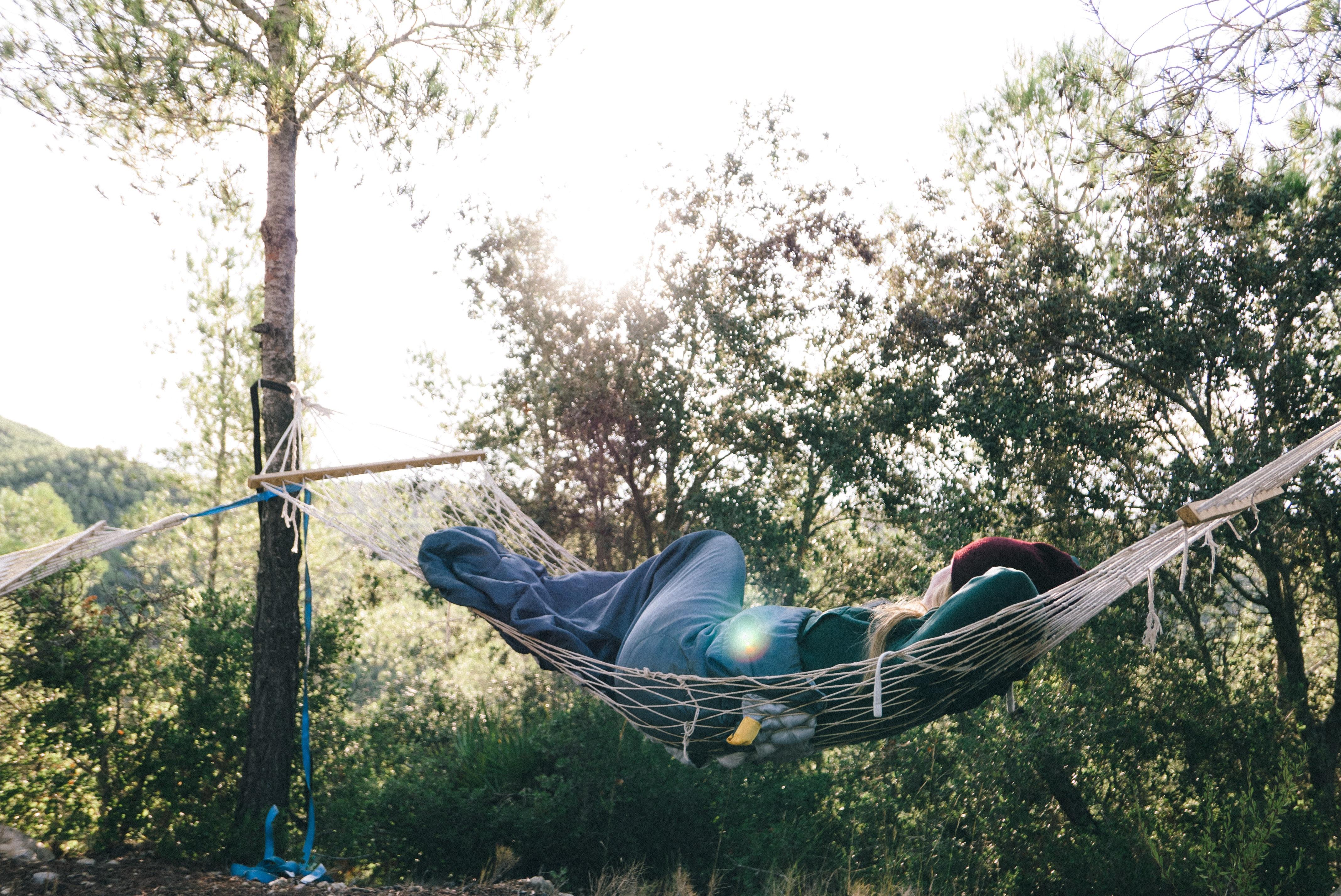 woman lying on white hammock