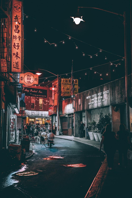 people between gray buildings during nighttime