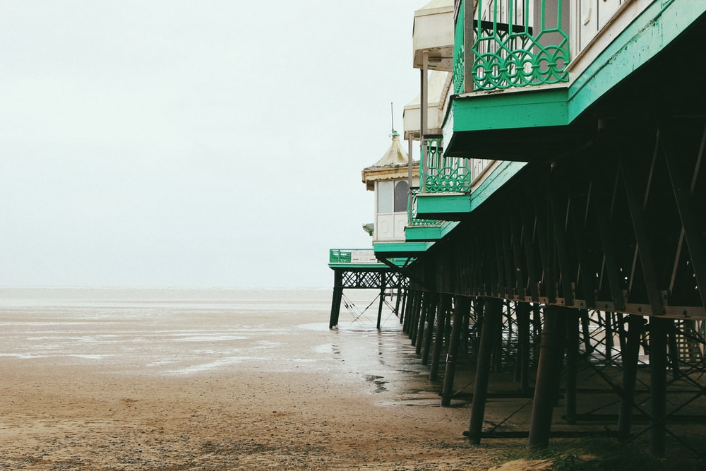 architectural photography of green and white building on seashore