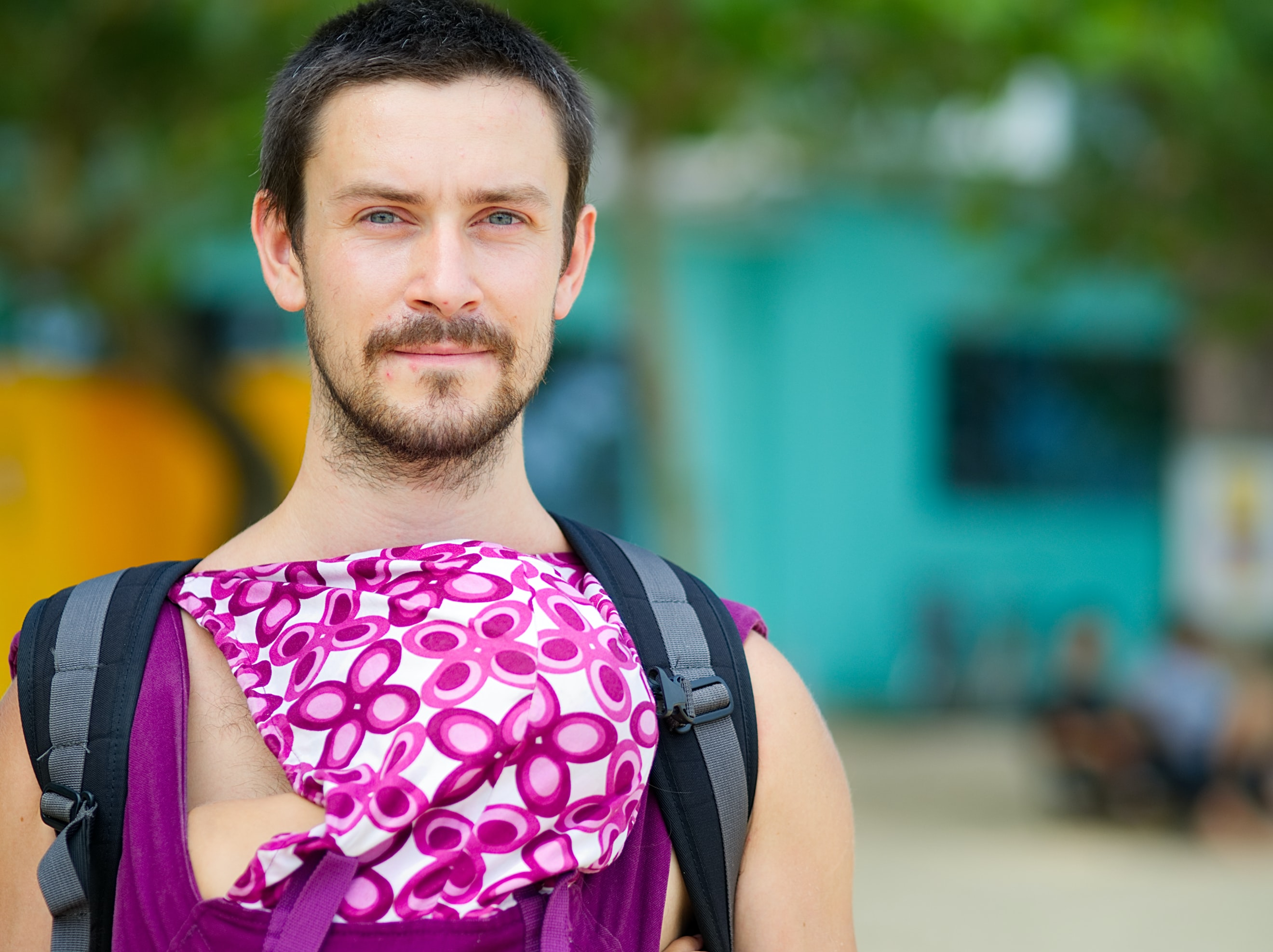 selective focus closeup photography of man in purple and white floral sleeveless shirt and black-and-gray backpack