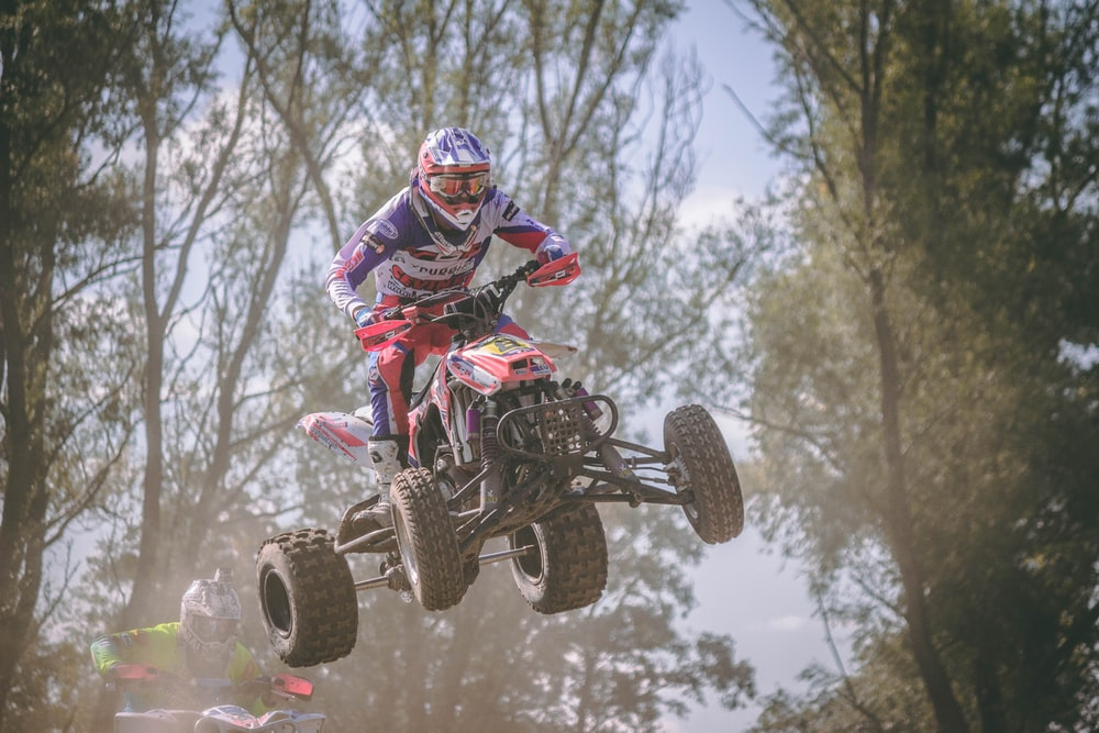person riding red and black ATV