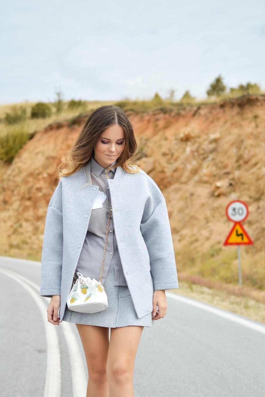 woman in gray coat and white sling bag walking on asphalt road during daytime
