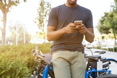man holding smartphone leaning on bicycle during daytime