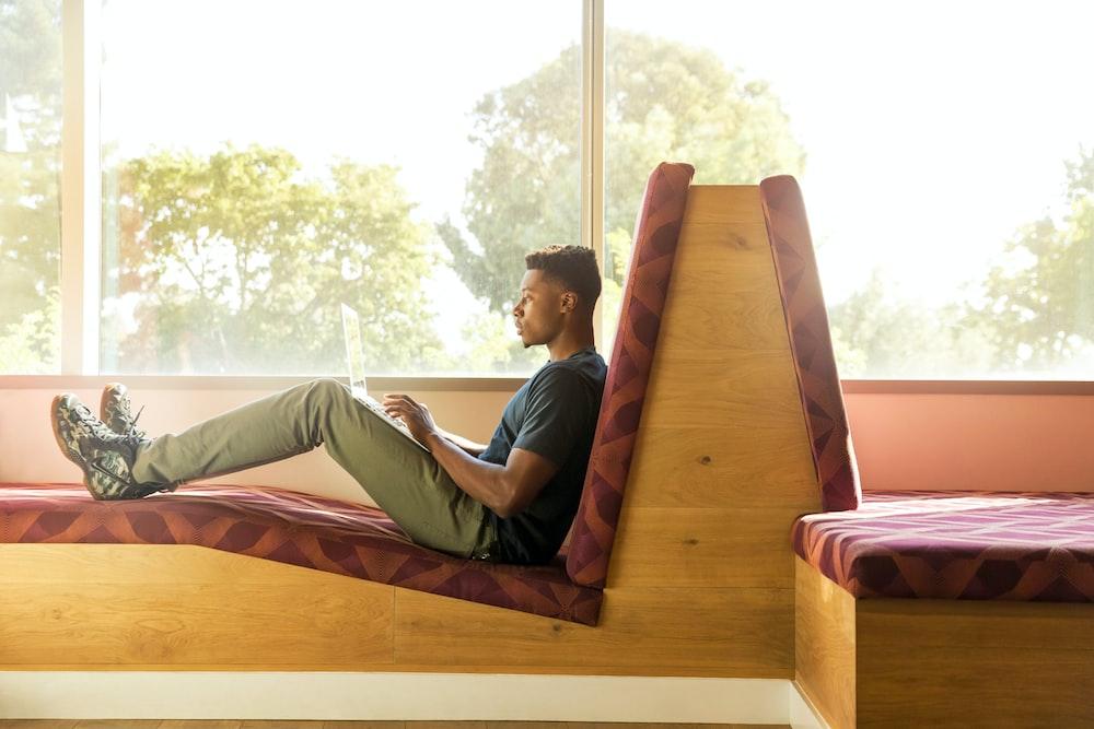 man sitting on red cushion beside window