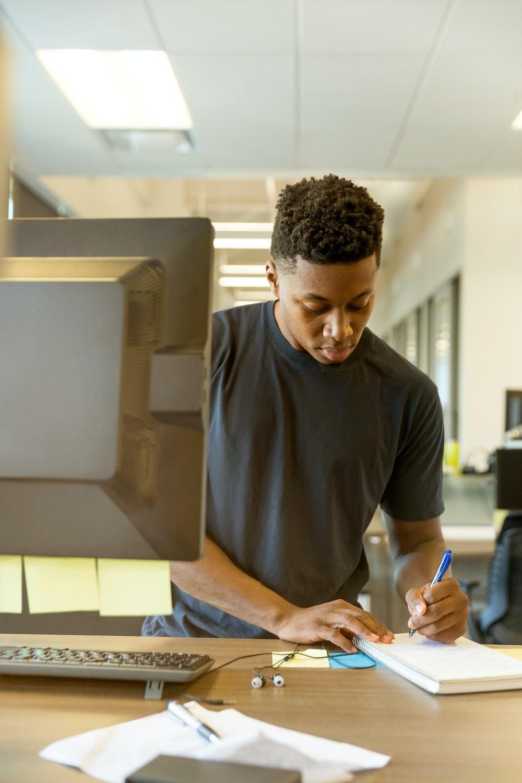 man writing on white paper