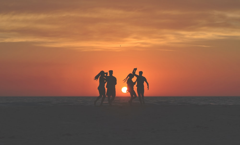 silhouette photo of four people dancing on sands near shoreline