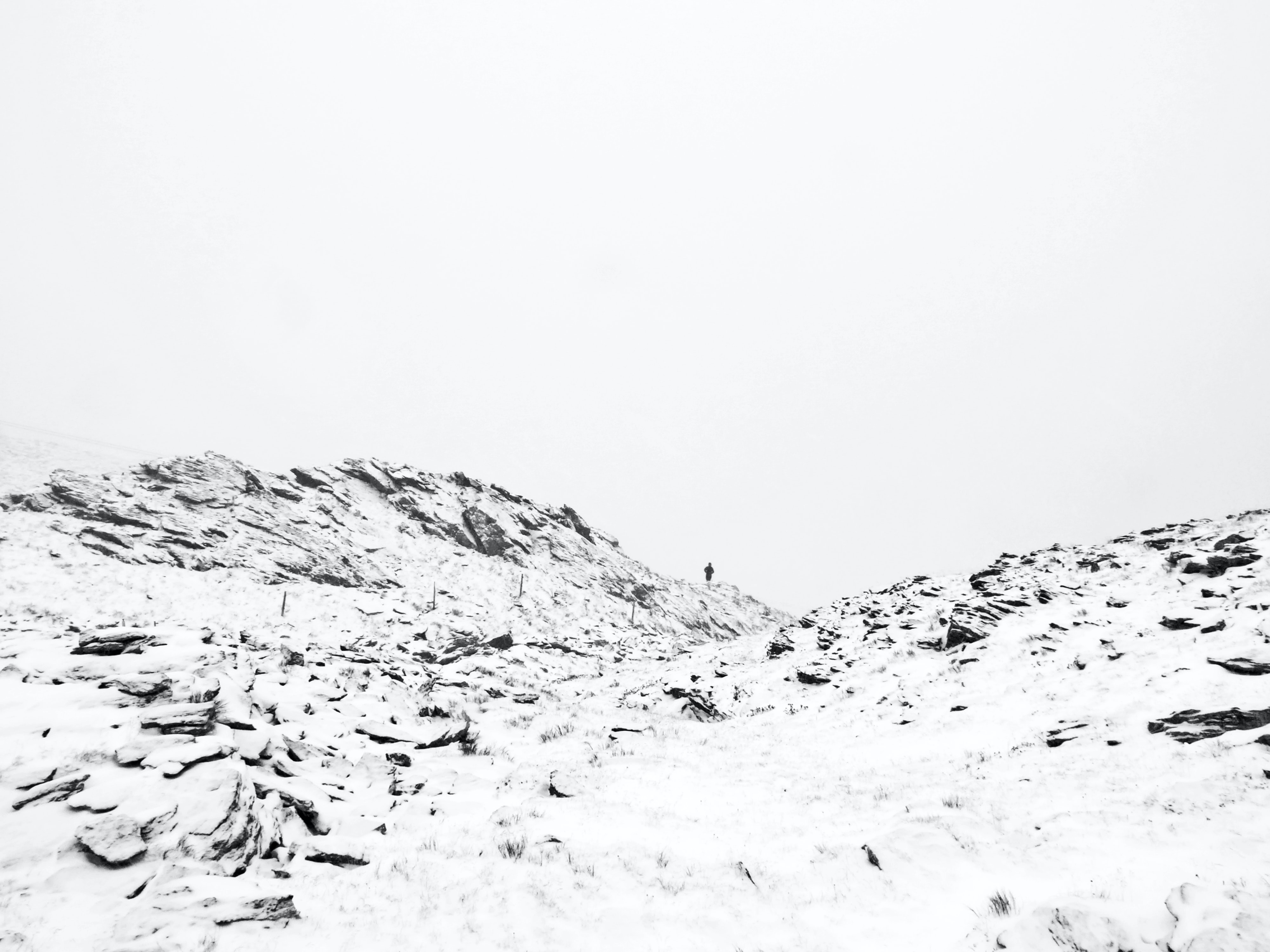 mountain covered with snow under white sky