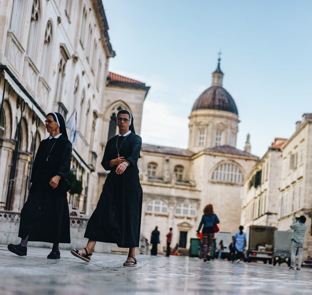 two nun walking in front of cathedral