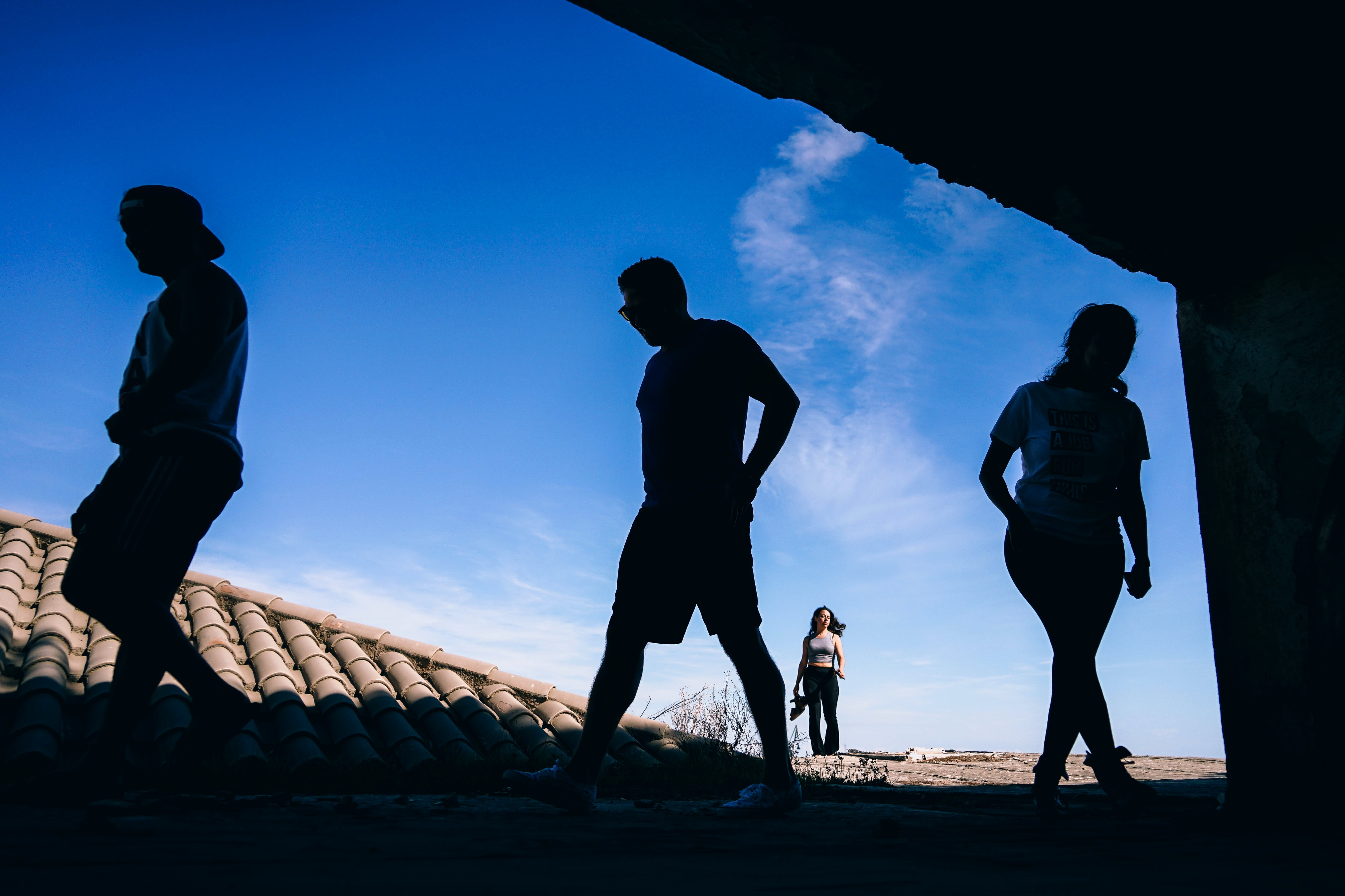 silhouette of three person walking over brown roof during daytime