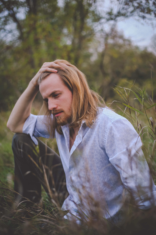 man sitting on green grass touching hair during daytime