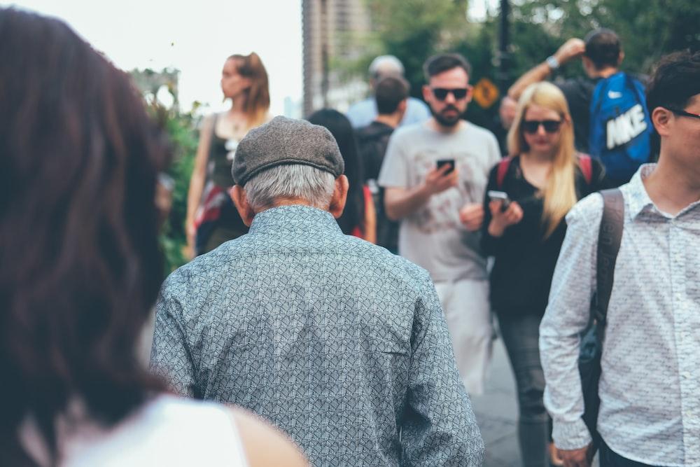 man wearing teal collard shirt walking through couple of people