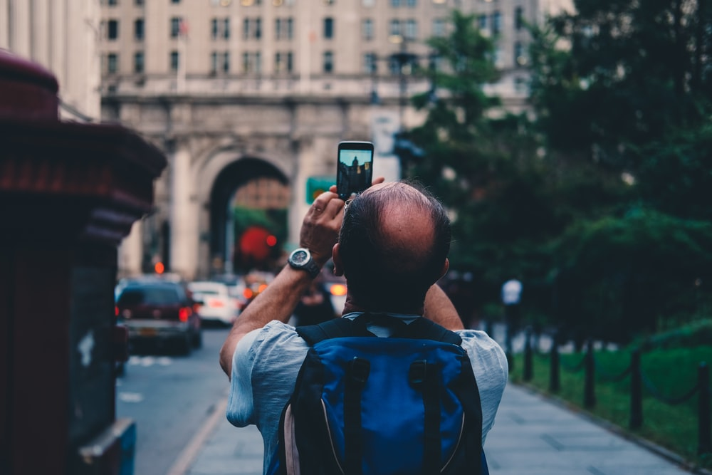 man taking a photo of white high-rise building at daytime