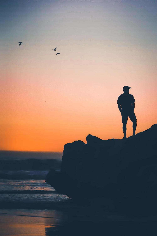 man standing on rock near on seashore