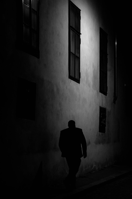 man walking beside gray concrete wall during night time