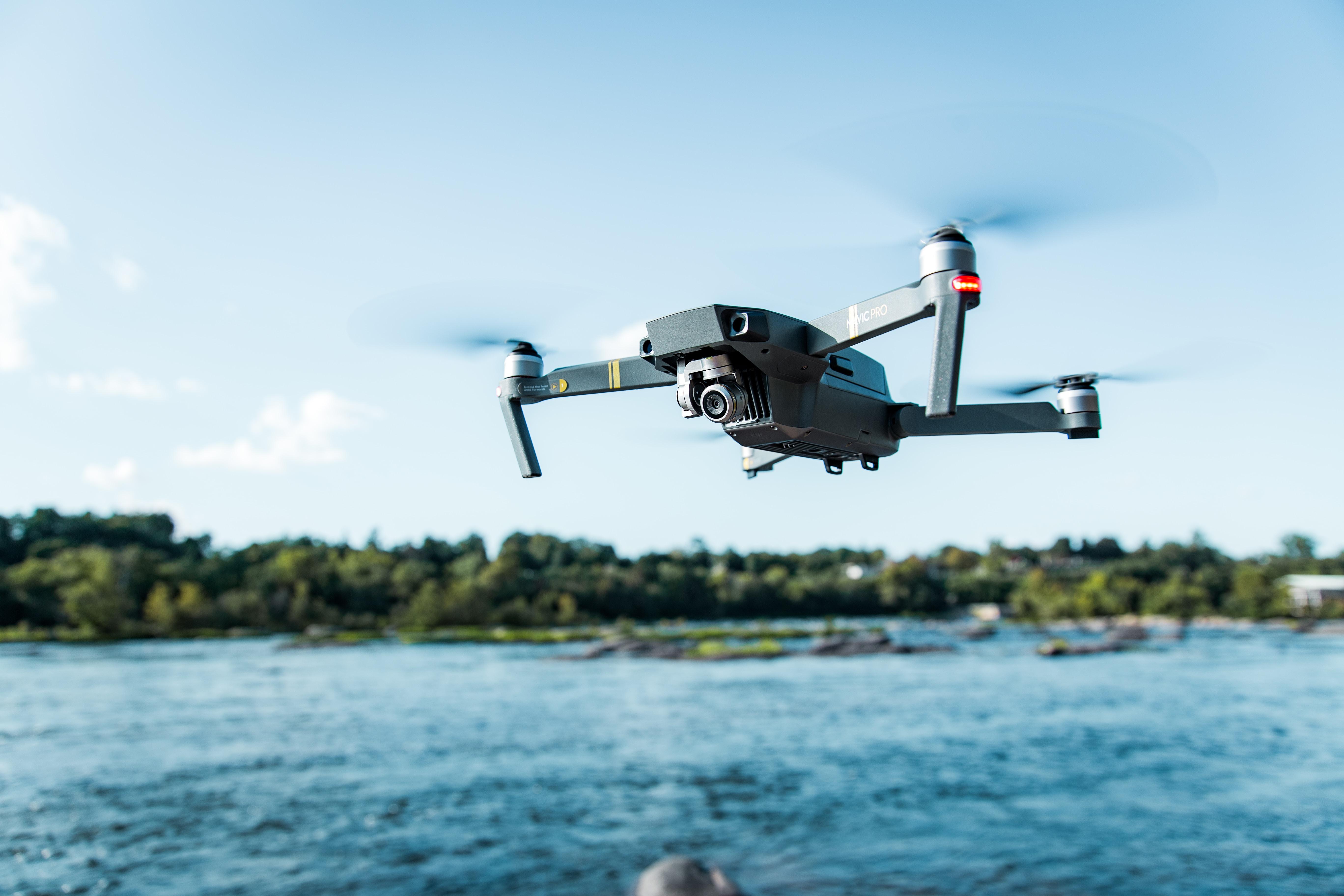 black DJI Mavi quadcopter near body of water