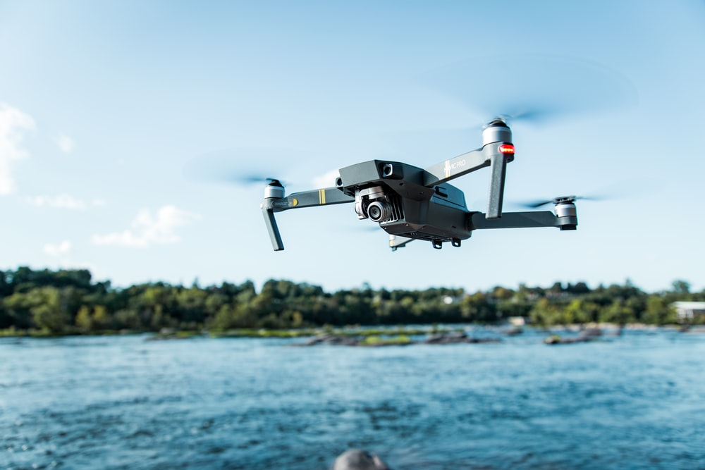 black DJI Mavi quadcopter near body of water