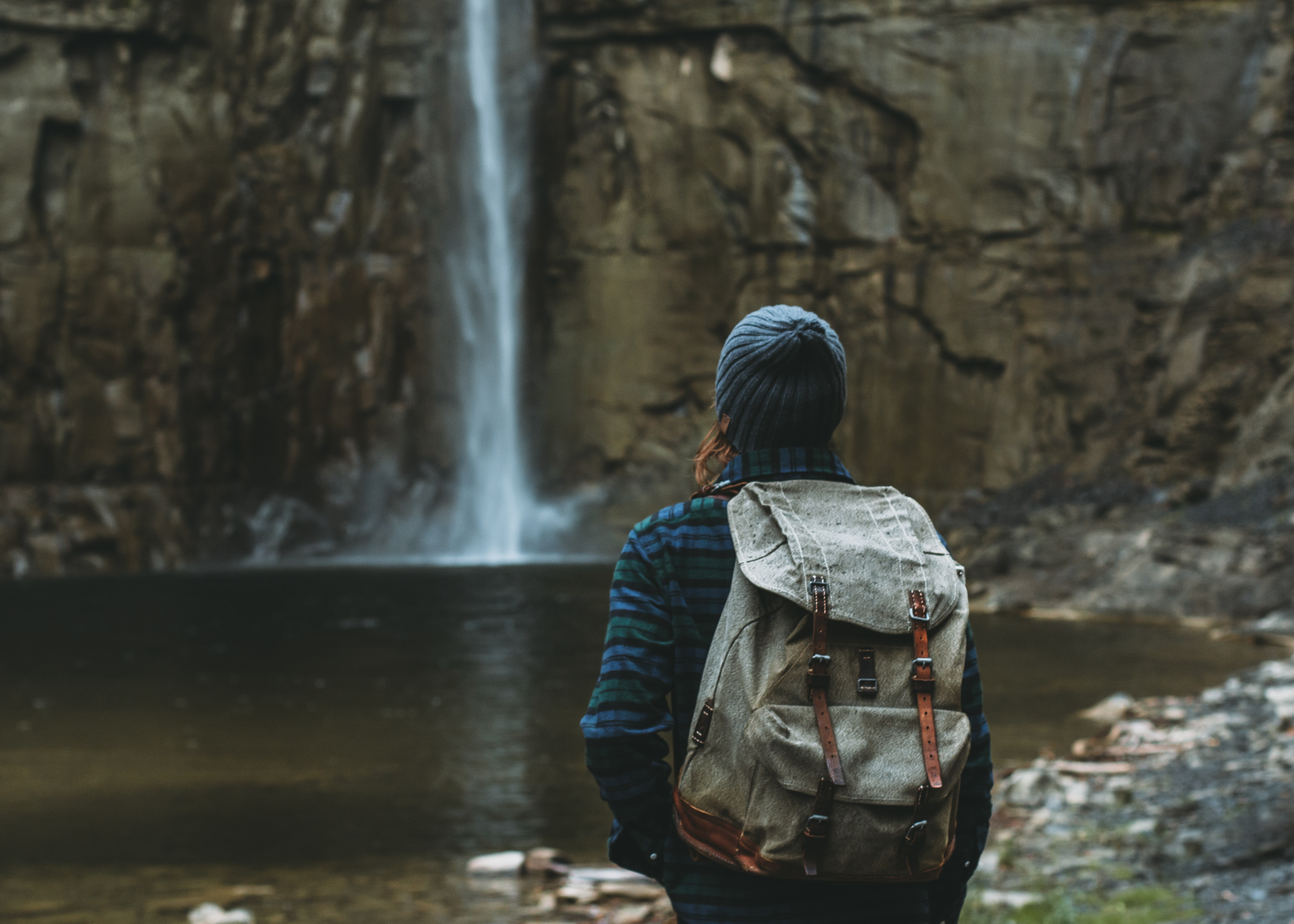woman with backpack facing waterfalls