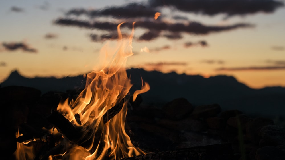 bonfire overlooking silhouette of mountain golden hour photography